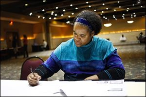 Toledo resident Holly Matthews fills out paperwork during a job fair held on Monday by Gabriel Brothers Inc. at the Ramada Toledo Hotel. Gabe's will be opening a new store in Sylvania Township.