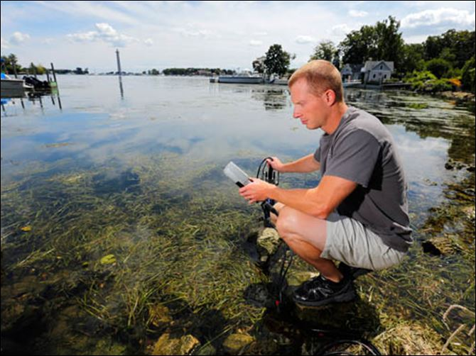 SPT  UTalgaedoctor Justin Chaffin, who has a doctorate degree from the University of Toledo, tests water at Put-in-Bay. Chaffin says he's always wondered what was in Lake Erie besides walleye and perch.