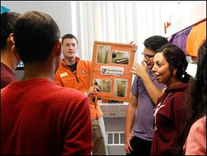 BGSU student volunteer Mike Reilly, left, talks about residential life and holds a picture of the dorm restroom and shower facilities in Kohl Hall to Western International High School. Antonio Gallegos, center and Alyssa Vasquez, right, listen.