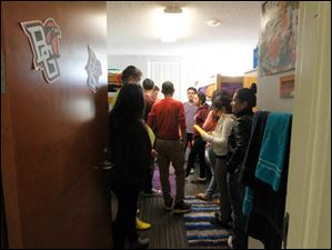 Western International High School students squeeze into a dorm room in Kohl Hall to hear about residential life while on a scavenger hunt.