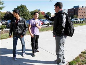 Western International High School students Juan Flores, 16, left, and Antonio Gallegos, right, listen as Ben Sloan, right, a BGSU sophomore from Loudonville, Ohio, gives their team directions to a dorm room while on a scavenger hunt.