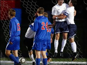 St. John's Jesuit's Cole Myers (8), left, celebrates scoring a goal with teammate Camden Buescher (7).