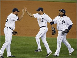 Detroit Tigers relief pitcher Joaquin Benoit, left, greets teammates Omar Infante and Prince Fielder, right, after the Tigers' 8-6 win over the against the Oakland Athletics in Game 4 of baseball's American League division series in Detroit.