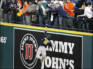 Fans reach for the ball as Oakland Athletics right fielder Josh Reddick stretches out to try to  grab it during the seventh inning of Game 4 on Tuesday, forcing an official review of the solo home run by Detroit Tigers' Victor Martinez on the grounds of possible fan interference. The homer stood.
