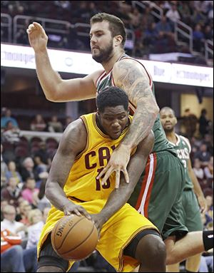 Milwaukee's Miroslav Raduljica, top, fouls Cleveland's Anthony Bennett during the first half. Bennett scored seven points.
