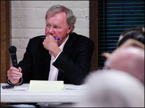 John Irish listens to a question he directed at mayoral candidates Mayor Mike Bell and D. Michael Collins.