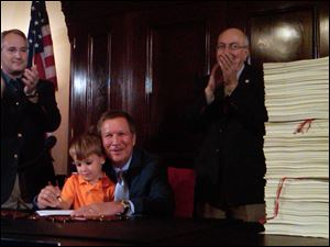 Felix Falco Plouck, 4, the son of a Cabinet member, helps Ohio Gov. John Kasich sign the state's $62 billion, two-year budget on June 30 in Columbus, Ohio. Kasich is flanked by, state Sen. Keith Faber, left, and House Finance Chairman Ron Amstutz, right.