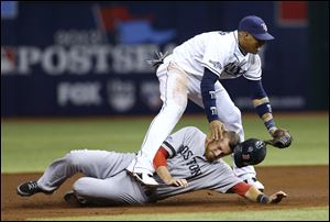 Boston Red Sox's Will Middlebrooks (16) slides under Tampa Bay Rays shortstop Yunel Escobar (11) after he was tagged out on a double play in the third inning.