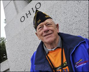 Honor Flight of Northwest Ohio member Ned Ammons  smiles under the Ohio section of the World War II Memorial on Wednesday in Washington.