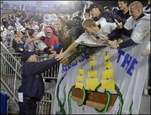 Penn State head coach Bill O' Brien, left, thanks fans in the student section of Beaver Stadium.