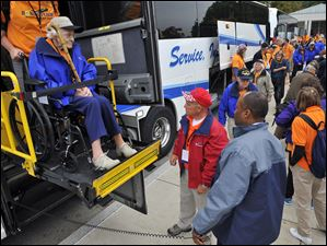 Army veteran Betty Reynolds  is helped off the bus at the World War II Memorial.