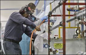 Employees at Sheffield Platers Inc. work on the factory floor in San Diego. Since the shutdown which started on Oct. 1, the company has focused on filling previously approved purchase orders, but if the government remains closed, President Dale L. Watkins Jr. says there could be layoffs among his 70 workers.