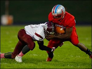 Bowsher's Steve Johnson (33) is tackled by Scott High School player Roy Lindsay (20) during the first quarter.