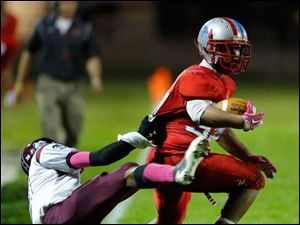 Bowsher's Steve Johnson (33) is dragged out of bounds by Scott High School player Roy Lindsay (20.