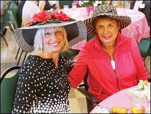 SOC pollyfox28p Joan Tobias, left, and Lonna Mikesell, both of Sylvania, right, sported large hats during a luncheon to support the Polly Fox Academy on Saturday, Sept. 28, 2013, at the Sylvania United Church of Christ. Several dozen women sported fancy hats to the luncheon.  THE BLADE/KATIE RAUSCH