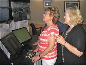 Barb Fletcher tries her hand at the demonstration maritime simulator with Katherine LaGrange looking on.  Both are members of Harbor View Yacht Club.