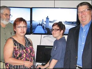 Pictured left to right, David Brown, Betty Osenbaugh, Alexis Knapp, and Victor Tufts.  Victor Tufts, Customer Support Manager for VSTEP/Nautis, (right)  watches Maritime  Academy of Toledo Cadet Alexis Knapp (center) play on the maritime demonstration simulator, along with David Brown and Betty Osenbaugh.