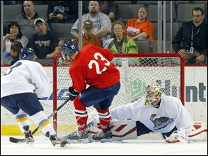 Walleye goalie Mac Carruth (35) blocks a shot by Wings player Justin Taylor (23) during the first period.