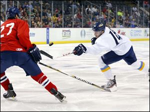 Walleye player  Kevin Lynch (14) shoots against Wings player Steve Whitely (27) during the first period.