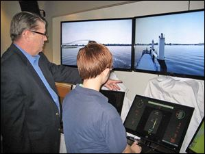 Victor Tufts, Customer Support Manager for VSTEP/Nautis, shows Maritime Academy of Toledo cadet, Alexis Knapp the maritime demonstration simulator.