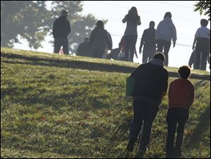 Long shadows are cast as two spectators climb a hill to watch runners.