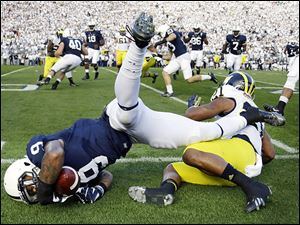 Penn State's Jordan Lucas, left, falls out of bounds after being tackled by Michigan's Jeremy Gallon after inter-cepting a pass during the first quarter.