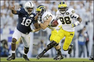 Michigan quarterback Devin Gardner (98) scrambles for a seven-yard gain.