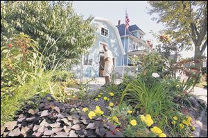 David Johnson maintains a garden at the corner of his business. At left are peach trees.