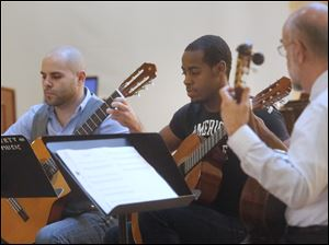 Michael Ziegler, left, and Denzell Anderson, center, played a classical guitar piece with their teacher Ken Hummer during Lourdes' Fall Music Showcase.