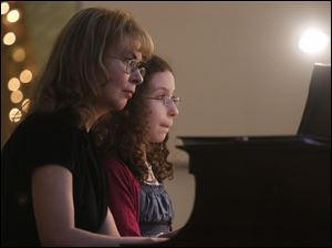 Olga Topuzova-Meade, left, played the piano with her daughter Sasha, 10.