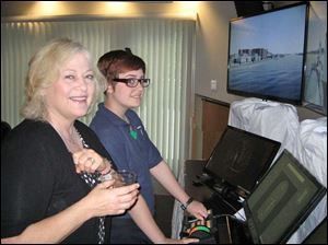 Harbor View Yacht Club member, Katherine LaGrange watches Maritime Academy of Toledo cadet, Alexis Knapp, on the demonstration maritime simulator.