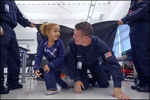Makayla Tidwell, 4, races Nick Wolfe, 16, of Genoa in a Penta program for Fire Prevention Week.  Preschoolers were learning the importance of crawling to get out of a building filled with smoke.