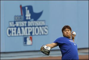 Dodgers starting pitcher Hyun-Jin Ryu practices in the outfield of Dodgers Stadium on Sunday in preparation for today's Game 3 against the St. Louis Cardinals. He says his arm feels strong.