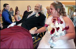 Scott Nagy hand-in-hand with his daughter Sarah is wheeled down the aisle as he gives his daughter away in marriage to Angelo Salvatore on Saturday at First Lutheran Church in Strongsville, Ohio.