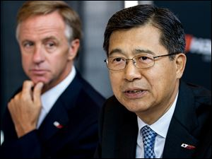 Seung Hwa Suh, vice chairman and CEO of Hankook Tire Co., speaks to reporters about the company's decision to build its first U.S. plant in Clarksville, Tenn., as Gov. Bill Haslam, left, looks on.