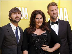 The band Lady Antebellum has postponed a planned November visit to Toledo. Band members are, from left, Dave Haywood, Hillary Scott, and Charles Kelley.