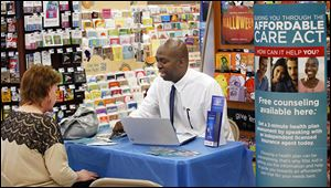 Joe Moore, a local independent insurance agent, talks with Jane York about the Affordable Care Act at Rite Aid on Sylvania Avenue in Toledo.