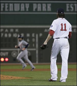 Red Sox starting pitcher Clay Buchholz watches as the Tigers' Alex Avila runs the bases after Avila hit a two-run home run in the sixth.