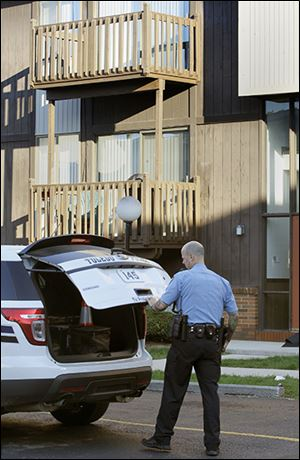 A Toledo police officer gets his gear outside the victim's apartment on West Alexis.