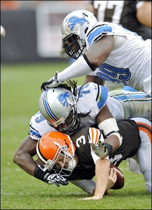 Browns quarterback Brandon Weeden is sacked by Lions defensive end Willie Young and C.J. Mosley in the third quarter. The second-year player has been criticized this season for holding the ball too long, making him one of the most-sacked quarterbacks in the league.