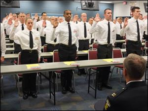 Members of the 61st Toledo Police Department Basic Police Officer Academy class takes their oath.