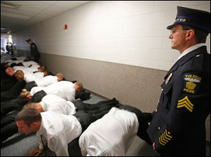 Sgt. Greg Mahlman, an instructor at the Toledo Police Academy, watches new cadets do push ups.