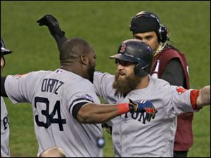 Boston Red Sox's David Ortiz celebrates with Mike Napoli after Napoli hits a home run in the seventh inning.