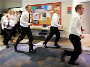Members of the  61st Toledo Police Department Basic Police Officer Academy class jog back to the classroom after doing pushups on the first day of training.