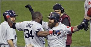 Boston's David Ortiz, center left, celebrates with Mike Napoli after Napoli's solo home run during the seventh inning provided the only run in Game 3 of the ALCS against the Tigers on Tuesday evening  in Detroit. The Red Sox lead the best-of-seven series 2-1.