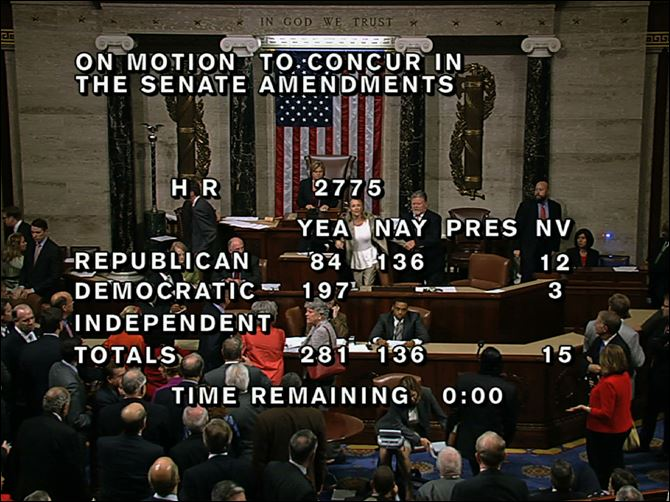 "In this image from House Television, with partial voting totals on the screen, a woman, at the rostrum just below the House presiding officer, seen between the ""yea"" and ""nay"" wording, is removed from the House chamber after she began shouting during the vote for the bill to end the partial 16-day government shutdown."