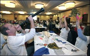 William Adamiak blows the vuvuzela as his NAMSA teammates, including Jennifer Shafer, second from right, and Kelly Jobe, cheer during The Blade Corporate and Community Spelling Bee.