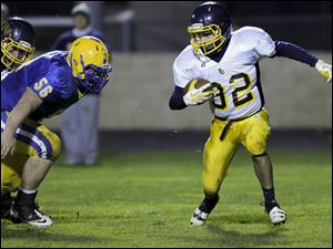 Toledo Christian junior Caleb Wotring (32) runs the ball as Northwood junior Myles Habel (56) chases him.