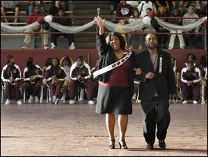 Scott principal and 1992 homecoming queen Treva Jeffries waves as she's escorted by 1992 homecoming king Dameon Austin.
