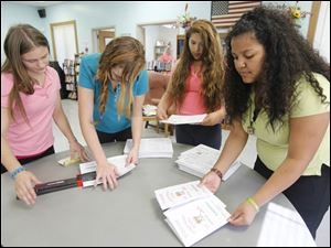 Eighth graders from Navarre Elementary from left to right Chyanne Papenfuse, 15, Ashley James, 13, Vanessa Perez, 13, and Elizabeth Gotay-Escalera, 13, lend a helping hand at the East Toledo Senior Center.